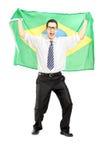Aufgeregter Mann, der eine brasilianische Flagge hält Stockfoto