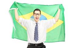 Aufgeregter Mann, der eine brasilianische Flagge hält Lizenzfreie Stockfotos