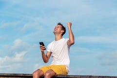 Aufgeregter Mann, der einen Smartphone hält und auf Linie auf einem tropischen Bestimmungsort gewinnt lizenzfreie stockfotos