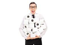 Aufgeregter Mann, der einen Stapel des Toilettenpapiers hält Stockbilder