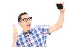 Aufgeregter Mann, der Eiscreme hält und selfie nimmt Stockbild