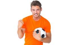 Aufgeregter Mann in der Orange, die Fußball halten zujubelt Lizenzfreies Stockbild