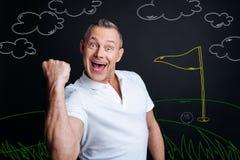 Aufgeregter Mann, der sein Glück beim Spielen des Golfs und des Gewinnens zeigt Lizenzfreie Stockfotos