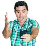 Aufgeregter Mann, der an seinem Telefon schreit Stockfotos
