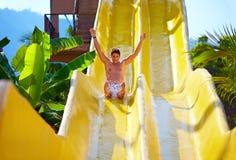 Aufgeregter Mann, der Spaß auf Wasserrutschen im tropischen Aquapark hat Stockbild