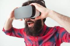Aufgeregter Mann, der VR-Sturzhelm hält Stockfotografie