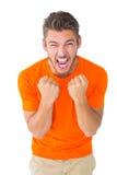 Aufgeregter Mann im orange Zujubeln Lizenzfreie Stockbilder