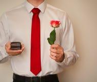 Aufgeregter Mann im Smokinghemd und in roter Bindung, einen Eheringkasten halten Stockbilder