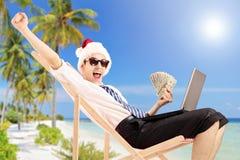 Aufgeregter Mann mit Sankt-Hut auf einem Strandstuhl, der Banknoten hält Lizenzfreies Stockbild