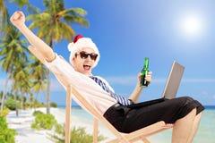 Aufgeregter Mann mit Sankt-Hut auf einem Strandstuhl, der ein Bier und ein w hält Stockfotos
