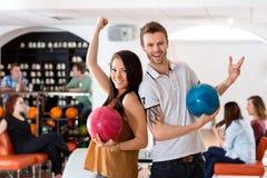 Aufgeregter Mann und Frau, die Bowlingkugeln hält Stockfotografie