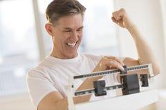 Aufgeregter Mann-zusammenpressende Faust bei der Anwendung der Gewichts-Skala Stockfotografie
