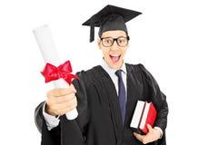 Aufgeregter männlicher Student im Aufbaustudium, der ein Diplom hält Stockfoto