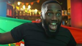 Aufgeregter schwarzer Fan, der portugiesische Flagge, freuenden nationalen Sportteamsieg wellenartig bewegt stock video footage