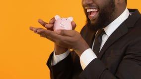 Aufgeregter schwarzer Mann im Anzug, der Sparschwein, Wartestartgewinn rüttelt stock video