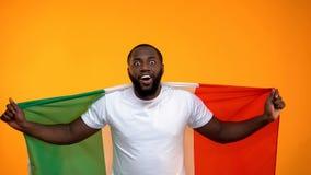 Aufgeregter schwarzer Sportfreund, der die italienische Flagge, jubelnd f?r Sieg, Patriotismus h?lt zu stockfotos