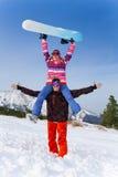 Aufgeregter Snowboarder mit Mädchen auf seinen Schultern Lizenzfreies Stockfoto