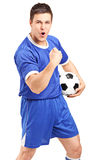 Aufgeregter Sportfreund, der einen Fußball und ein Gestikulieren anhält Stockfotografie