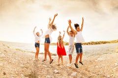 Aufgeregter Teenager, der Spaß auf dem Strand springt und hat stockbild
