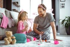 Aufgeregter Vater und Tochter, die zusammen mit Kosmetik spielt stockbild