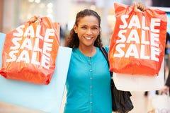 Aufgeregter weiblicher Käufer mit Verkaufs-Taschen im Mall Stockfotografie