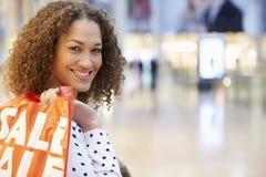 Aufgeregter weiblicher Käufer mit Verkaufs-Taschen im Mall Stockfotos