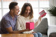 Aufgeregtes Öffnungsgeschenkboxempfangen der jungen Frau vorhanden vom Ehemann stockfotografie