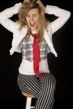 Aufgeregtes blondes Mädchen, das auf dem Schemel zieht ihr Haar sitzt Stockbild