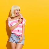 Aufgeregtes blondes Mädchen mit einem Getränk Lizenzfreies Stockfoto