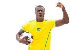 Aufgeregtes brasilianisches Fußballfan, das Ball halten zujubelt stockbild
