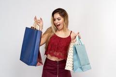 Aufgeregtes energisches helles blondes Modell zeigt breites Lächeln mit den weißen Zähnen und den Einkaufstaschen vom Speicher Stockbilder