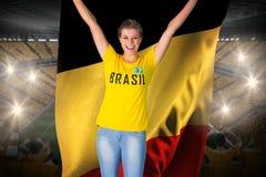 Aufgeregtes Fußballfan in Brasilien-T-Shirt, das Belgien-Flagge hält Stockfoto
