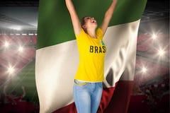 Aufgeregtes Fußballfan in Brasilien-T-Shirt, das Italien-Flagge hält Stockfoto