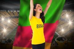 Aufgeregtes Fußballfan in Brasilien-T-Shirt, das Cameroon-Flagge hält Stockfotos
