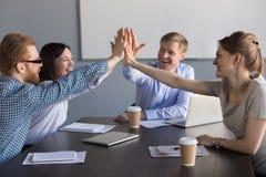 Aufgeregtes Geschäftsteam von den Angestellten, die Hoch fünf während des meeti geben lizenzfreies stockfoto