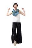 Aufgeregtes gewinnendes junges Mädchen, das lose Hose und bunten Schal mit den geballten Fäusten trägt stockbilder