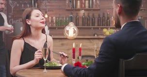 Aufgeregtes hübsches Mädchen, das mit ihrem Datum spricht und Abendessen genießt stock video