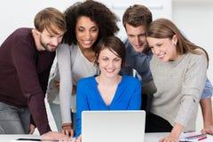 Aufgeregtes junges Geschäftsteam, das einen Laptop betrachtet Lizenzfreie Stockfotos