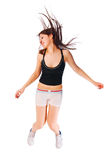 Aufgeregtes junges Mädchen, das auf Weiß springt Stockfotografie