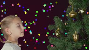 Aufgeregtes junges weißes Mädchen, das Weihnachtsbaum und mit dem glücklichen Schauen zum Tannenbaum verziert Vorbereiten für fro stock video footage