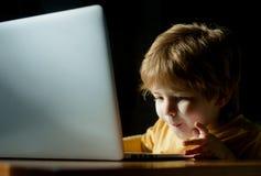 Aufgeregtes Kind nahe dem Laptopmonitor Interessante Informationen Digital-Lernen Schwarzer Hahn auf einem Wei? interessieren stockbild