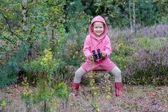 Aufgeregtes kleines Mädchen, das in der Hand mit Ferngläsern springt stockbild