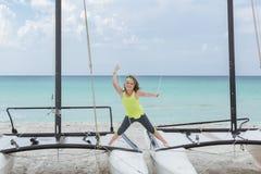 Aufgeregtes lächelndes kleines Mädchen, das auf Katamaran auf tropischem Hintergrund steht Stockfotos