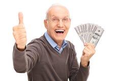 Aufgeregtes älteres haltenes Geld und einen Daumen aufgeben Stockfoto