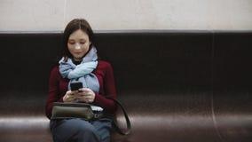 Aufgeregtes Mädchen, das auf dem Smartphone sitzt auf der Bank wartet den Zug an der Station simst stock video footage