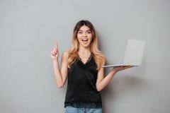 Aufgeregtes Mädchen, das Laptop hält und oben Finger auf copyspace zeigt Lizenzfreie Stockfotos