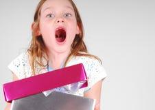 Aufgeregtes Mädchen mit Geschenk Stockbild