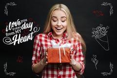 Aufgeregtes Mädchengefühl beim Erhalten eines wunderbaren Geschenkes beeindruckt Lizenzfreies Stockbild