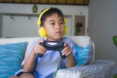 Aufgeregtes und glückliches spielendes Videospiel des lateinischen Jungen online mit den Kopfhörern, die den Kontrolleur genießt  lizenzfreie stockfotos