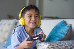 Aufgeregtes und glückliches spielendes Videospiel des lateinischen Kleinkindes online mit den Kopfhörern, die den Kontrolleur gen lizenzfreie stockbilder